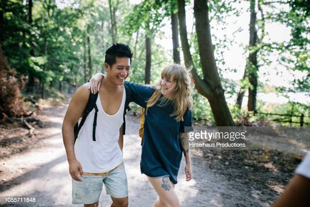 couple walking together in afternoon sun - arm around stock pictures, royalty-free photos & images