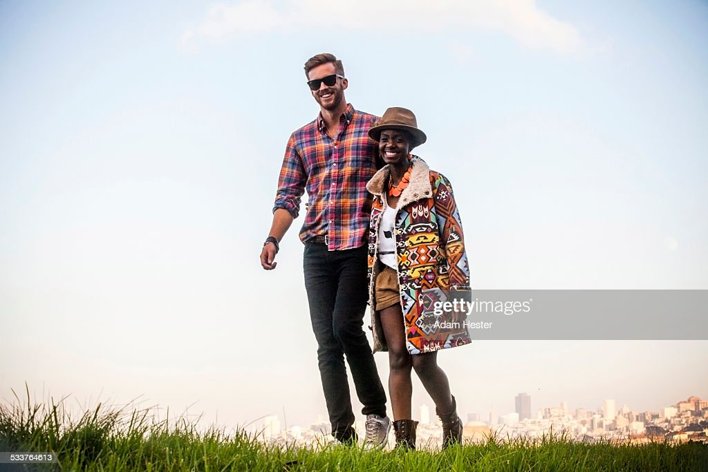 Couple walking together in grassy field : Foto stock
