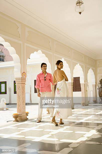 Couple walking together in hotel corridor, India