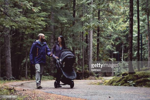 couple walking together in nature with their newborn - baby stroller stock pictures, royalty-free photos & images