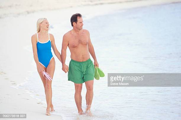 couple walking together on beach, holding sandals - green shorts stock photos and pictures