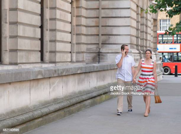 couple walking together on city street, london, united kingdom - travelstock44 stock pictures, royalty-free photos & images