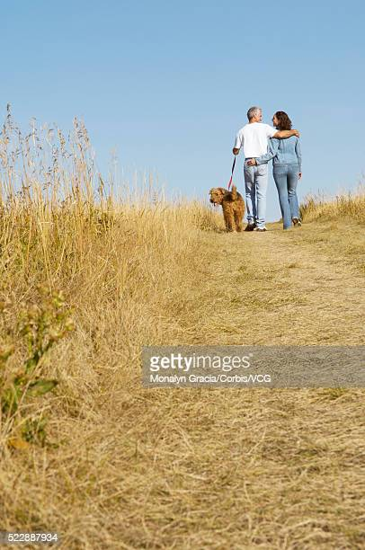 Couple walking together through a field
