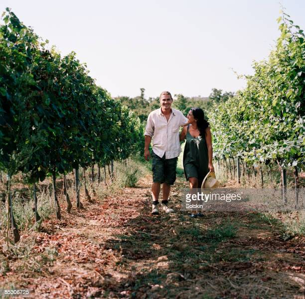 Couple walking together through field of wine stoc