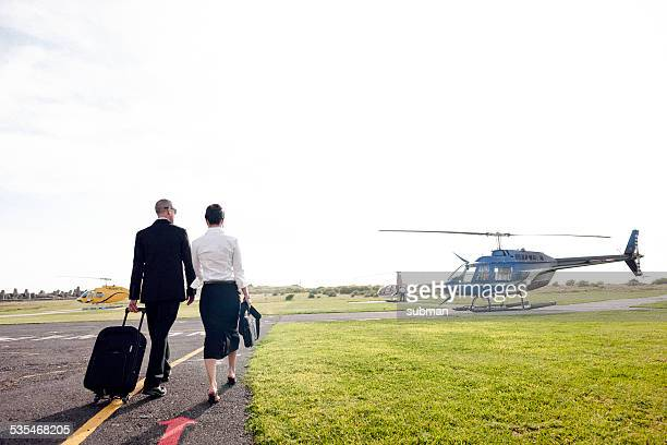 a couple walking towards a helicopter - helipad stock photos and pictures