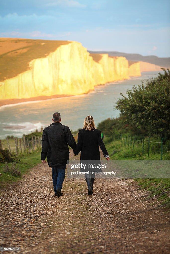 Couple walking towards cliff coastline : Stock Photo