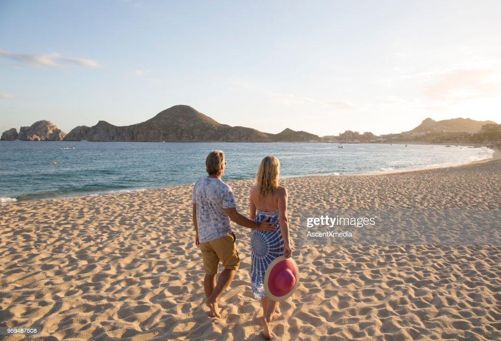 Paare, die in Richtung Hügel am Strand am Meer bei Sonnenuntergang : Stock-Foto