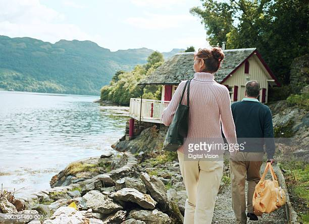 couple walking towards house by water, rear view - cottage exterior stock pictures, royalty-free photos & images