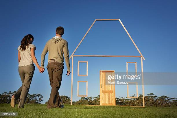 Couple walking towards vertical house outline