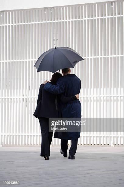 Paar zu Fuß unter Sonnenschirm