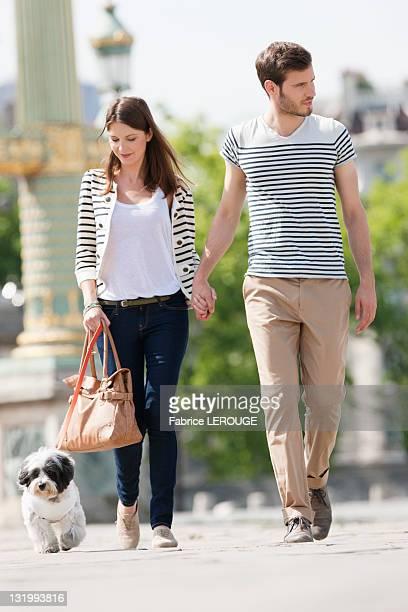 Couple walking with a puppy, Paris, Ile-de-France, France