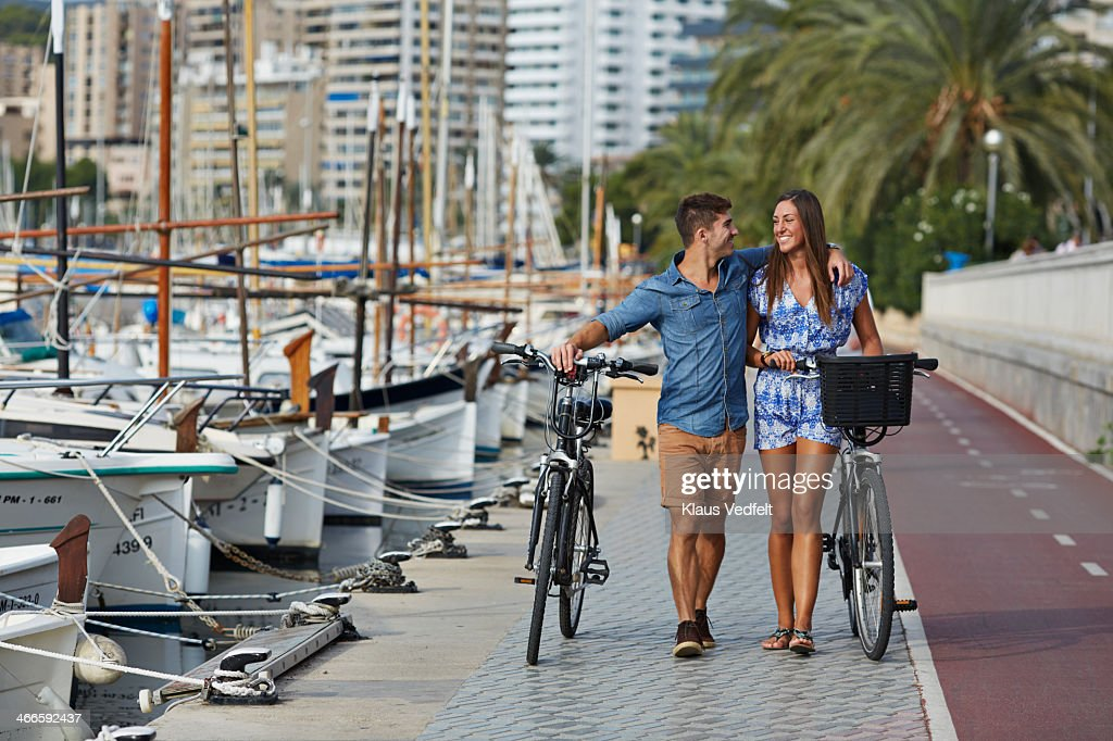 Couple walking with bikes at small harbor : Foto de stock
