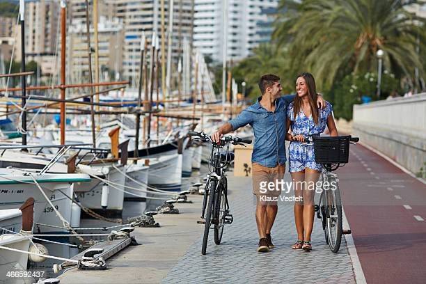 couple walking with bikes at small harbor - klaus vedfelt mallorca stock pictures, royalty-free photos & images