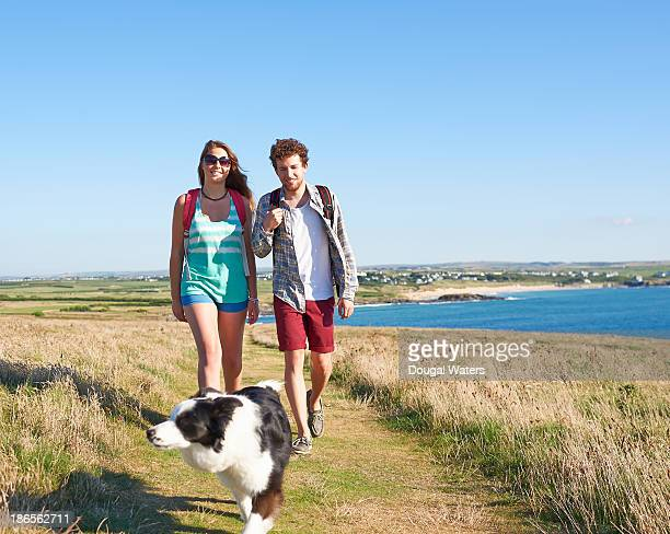 couple walking with dog along coastal path. - dougal waters stock pictures, royalty-free photos & images