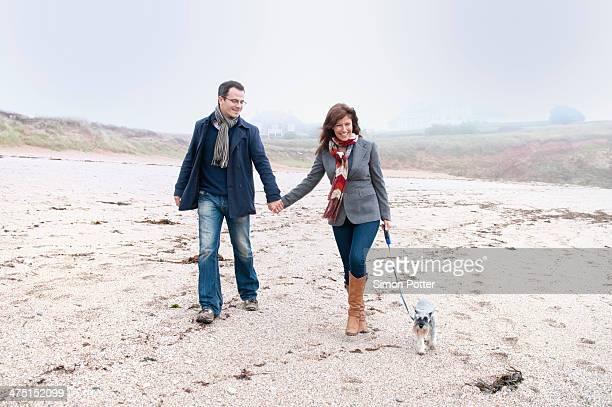 Couple walking with dog on beach, Thurlestone, Devon, UK