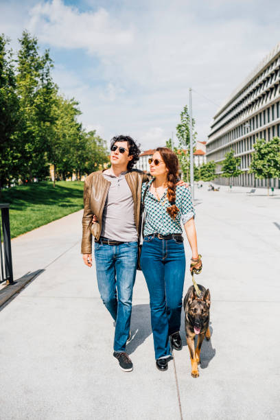 Couple walking with dog on city street during sunny day