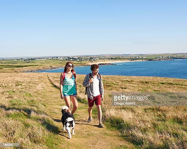 couple walking with dog. - ecoturismo foto e immagini stock