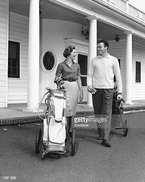Couple walking with golf carts in front of clubhouse