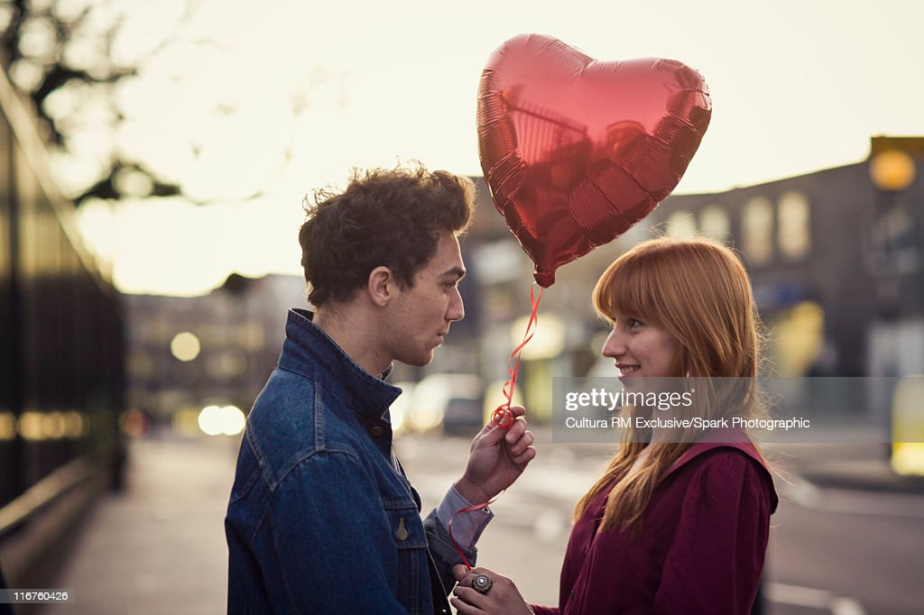 Couple walking with heart-shaped balloon : Stock Photo