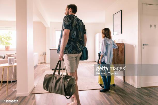 couple walking with luggage in apartment during staycation - 賃貸借 ストックフォトと画像