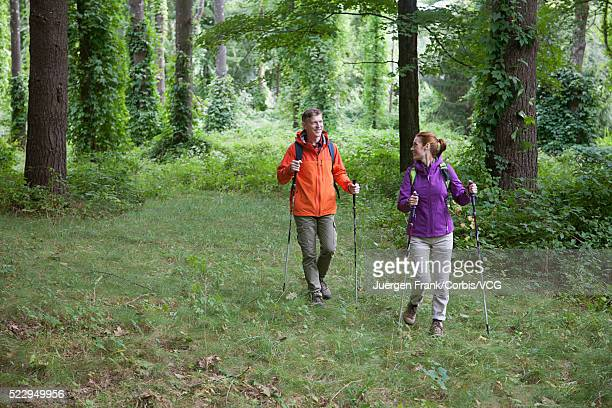 Couple walking with poles in forest
