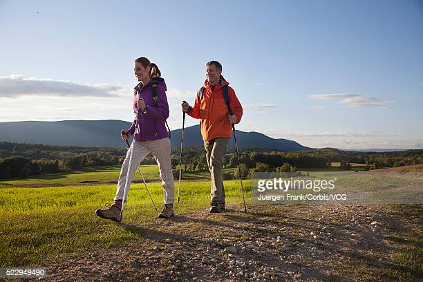 Couple walking with poles in meadow