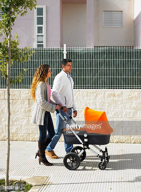 Couple walking with pram on pavement, Alicante, Spain,