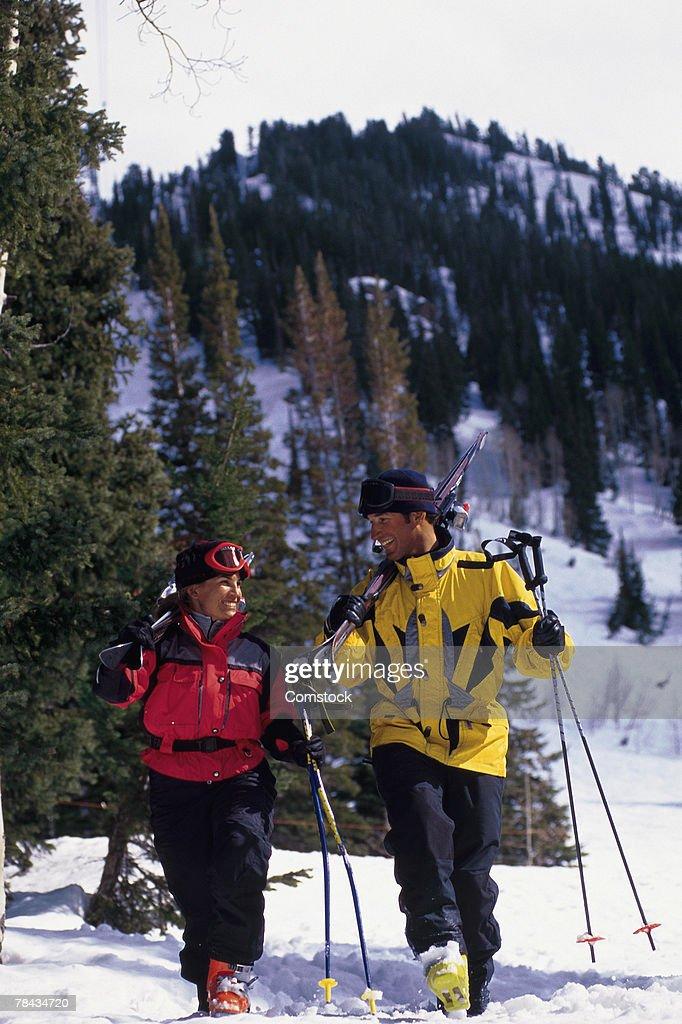 Couple walking with skis over snow : Stockfoto