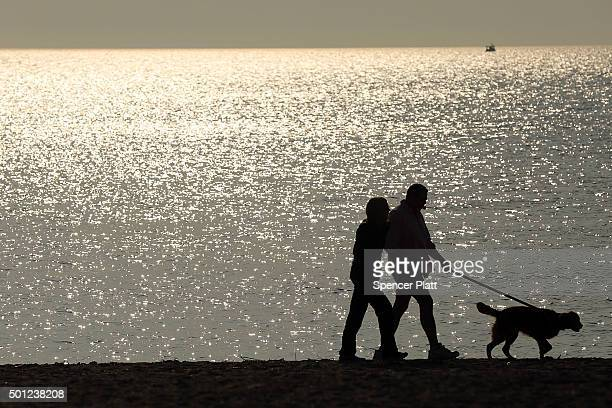 A couple walks a dog along a beach on December 13 2015 in Fairfield Connecticut Temperatures across much of the New York metropolitan area continued...