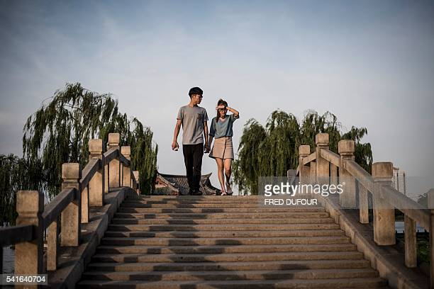 A couple walks across a bridge at Daming Lake in Jinan Shandong province on June 17 2016 Jinan is also called the 'Spring City' for its wellknown...