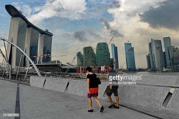 A couple walks across the bridge overlooking the skyscraper of the business district in Singapore on June 9 2010 Singapore economy expected to grow...