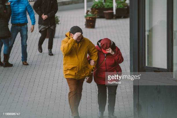 A couple walks against strong wind upon storm Sabine arrival on February 9 2020 in Cologne Germany