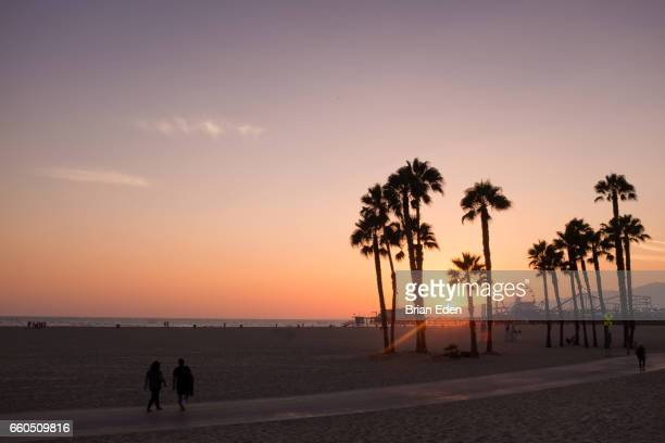 a couple walks along the beach at sunset in santa monica, california - santa monica stock pictures, royalty-free photos & images