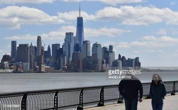 A couple walks along the Hudson river with view of lower Manhattan and One World Trade Center on April 22 2020 in Hoboken New Jersey The World Health...