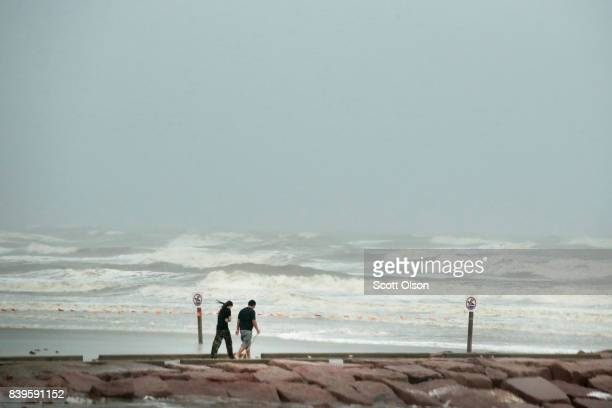 A couple walks along the shoreline as it is battered by wind and rain from Hurricane Harvey on August 26 2017 in Galveston Texas Harvey which made...