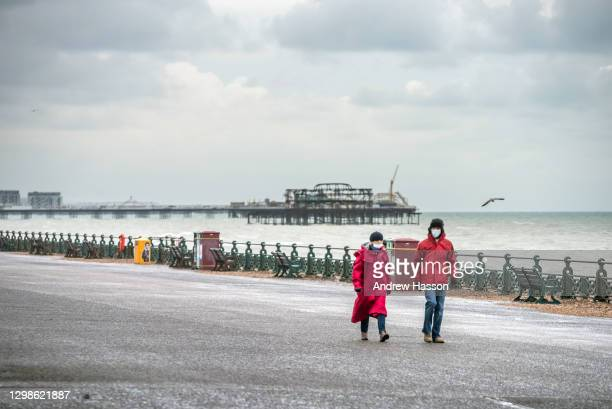 Couple walks as cold and windy conditions meant the seafront in Brighton was almost completely deserted this morning on January 26, 2021 in the city...