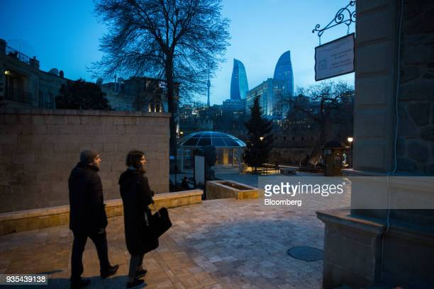 A couple walks as the Flame Towers stand in the background in the Old City of Baku Azerbaijan on Friday March 16 2018 Azerbaijan's economy barely...