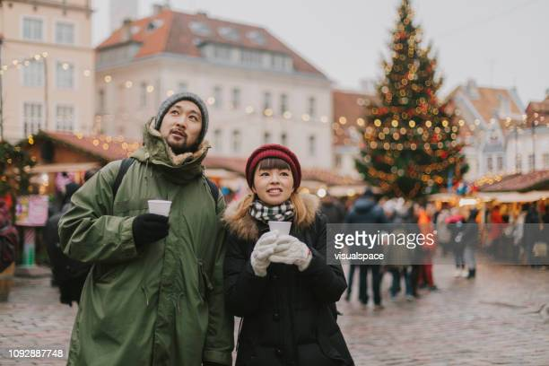 Couple walks at Christmas market and drinks mulled wine