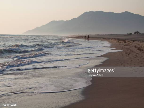 """a couple walks at sunset along the sandy beach of patara on mediterranean """"turquoise coast"""", aka """"turkish riviera"""", in turkey - kas stock pictures, royalty-free photos & images"""