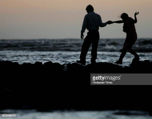 A couple walks back to the shore after the sunset at Bandstand on March 26 2006 in Mumbai India