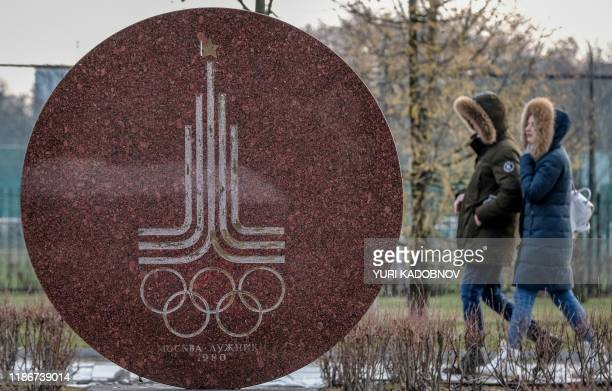Couple walks behind a monument featuring the emblem of the 1980 Moscow Olympics near the Luzhniki stadium in Moscow on December 6, 2019. - The...
