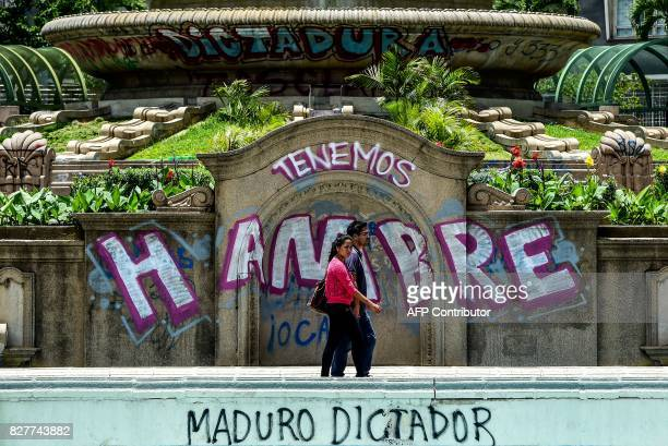 TOPSHOT A couple walks by graffitis reading 'We Are Hungry' and 'Maduro Dictator' in Caracas on August 8 2017 Recent demonstrations in Venezuela have...