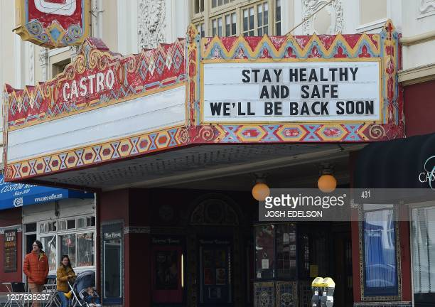 A couple walks by the Castro theater with their baby in San Francisco California on March 17 2020 Millions of San Francisco area residents last...