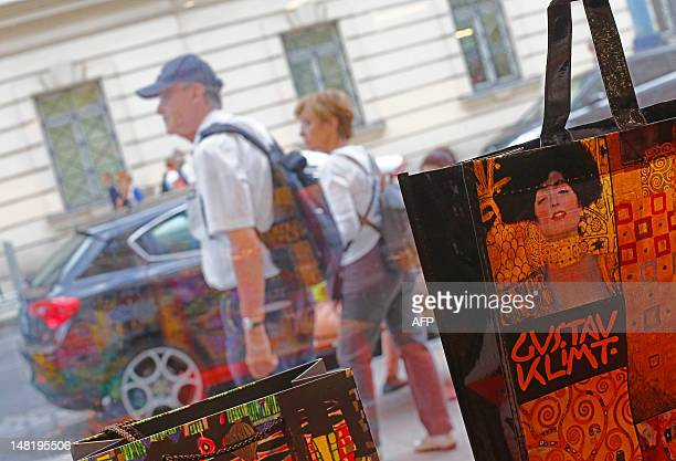 A couple walks by the window of a shop selling souvenirs of Austrian artist Gustav Klimt in Vienna on July 11 2012 On his 150th birthday Vienna's...