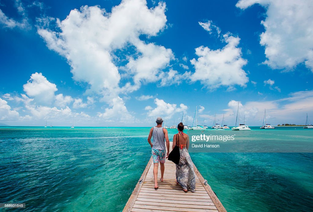ANEGADA ISLAND, BRITISH VIRGIN ISLANDS, CARIBBEAN. A couple walks down a long dock surrounded by teal sea and blue sky. : Stock-Foto
