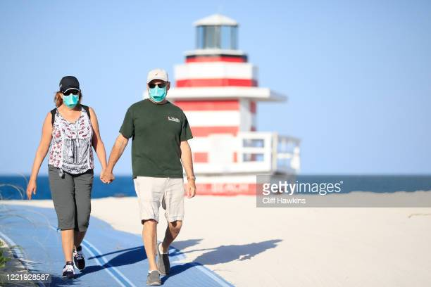 A couple walks from the closed beach in South Pointe Park on April 29 2020 in Miami Beach Florida The city of Miami Beach partially reopened parks...