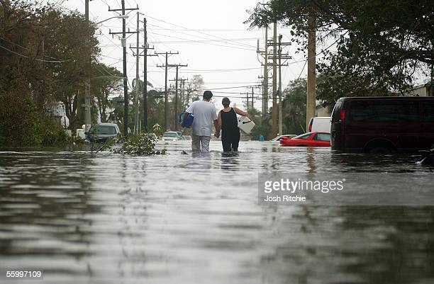A couple walks hand in hand as they brave flood waters several feet deep aong South Street after Hurricane Wilma passed through in the early morning...