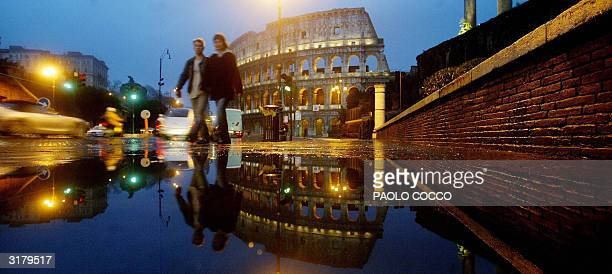 A couple walks in a flooded central Rome street with the ancient Colosseum in the background 31 March 2004 Heavy rain hit the Italian capital during...