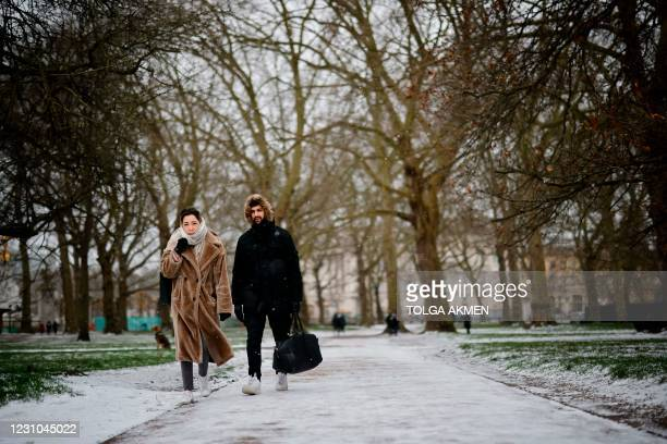 Couple walks in a park in the snow in central London on February 8, 2021. - Cold weather swept across northern Europe bring snow and ice.