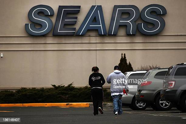 A couple walks into a Sears store on December 27 2011 in Milford Connecticut Sears Holdings Corp has announced that it plans to close between 100 and...